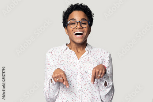 Fototapeta Head shot excited African American girl in glasses pointing down obraz