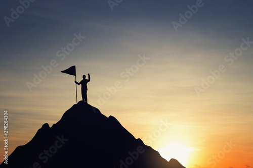 Silhouette of businessman holding a flag on top mountain, sky and sun light background. Business success and goal concept.