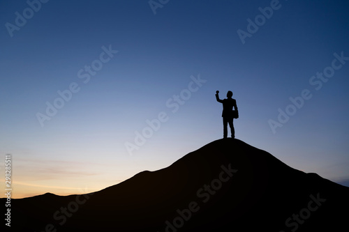 Fototapeta Silhouette of businessman raising his hand to celebrate success on top mountain, sky and sun light background. obraz na płótnie