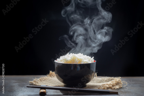 Cooked rice with steam in black bowl on dark background,hot cooked rice in bowl Wallpaper Mural