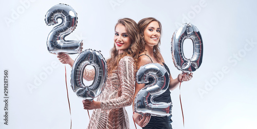 Happy young women with metallic 2020 balloons on white background Canvas Print