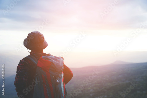 Foto auf Gartenposter Dunkelbraun man hiking traveling stand and watch the sunset on top of cliff in travel Lifestyle wanderlust adventure with backpack enjoying on peak mountain. Tourist traveler on background valley landscape view.