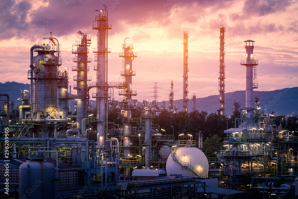 Fototapeta Gas refinery plant on sunset sky background, Manufacturing of petrochemical industrial plant with distillation tower and gas storage sphere tank