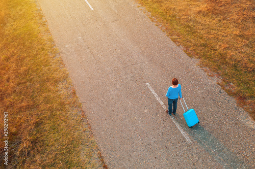 Pinturas sobre lienzo  Woman pulling travel suitcase luggage on road in autumn sunset