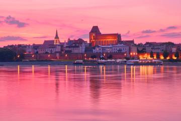 Torun old town in Poland, UNESCO world heritage site, with illumination, reflected in Vistula river on pink sunset.