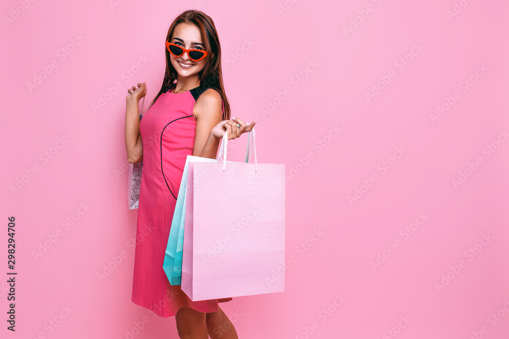 Fototapety, obrazy: young beautiful woman, in pink dress and sunglasses, with shopping on pink background