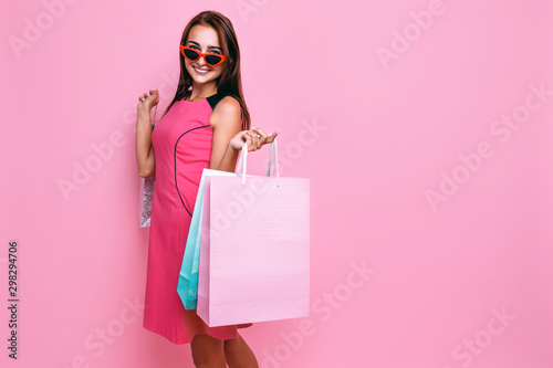 young beautiful woman, in pink dress and sunglasses, with shopping on pink backg Canvas