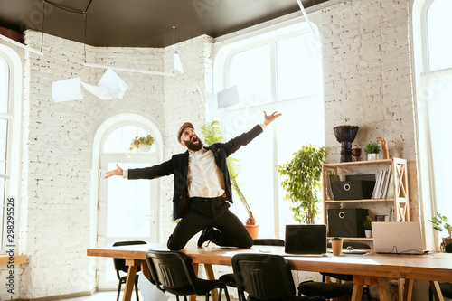 Young caucasian businessman having fun dancing break dance in the modern office at work time with gadgets. Management, freedom, professional occupation, alternative way of working. Loves his job. - 298295526