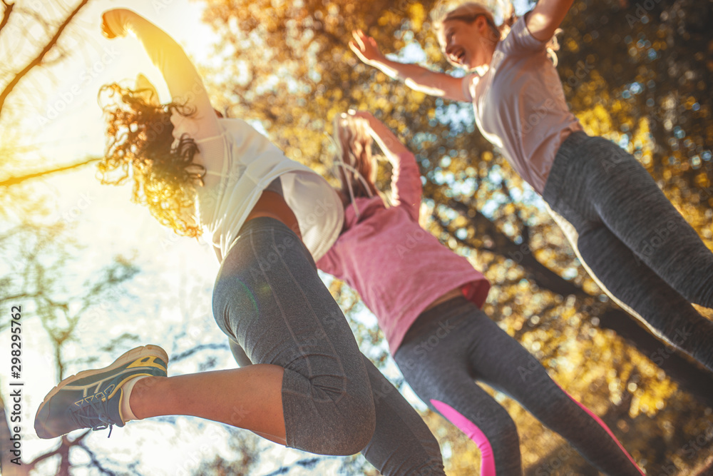 Fototapety, obrazy: Group of female friends jump around at the city park.Relaxing and making fun after jogging.