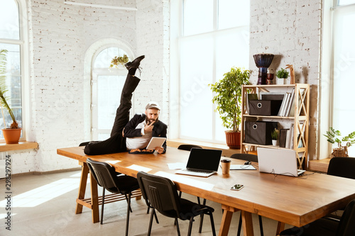Young caucasian businessman having fun dancing break dance in the modern office at work time with gadgets. Management, freedom, professional occupation, alternative way of working. Loves his job. - 298297924