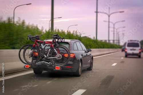 Photo  Car transports bicycles on a rack on highway in early morning