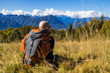 A man with a backpack sits on a hill among beautiful alpine landscapes. The man is blurred. Mountains and horizon in focus.