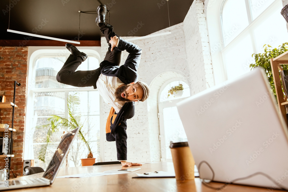 Fototapety, obrazy: Young caucasian businessman having fun dancing break dance in the modern office at work time with gadgets. Management, freedom, professional occupation, alternative way of working. Loves his job.