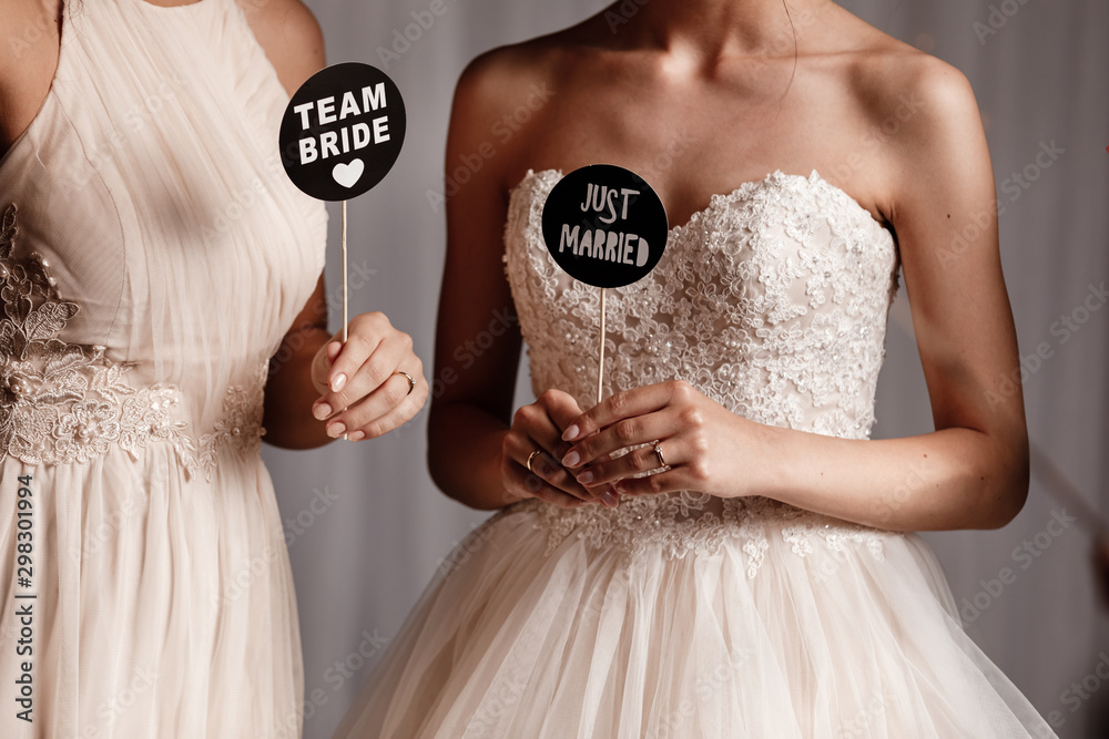 Fototapety, obrazy: Bride and her bridesmaid holding accessories for the wedding photo shoot. Wedding concept.