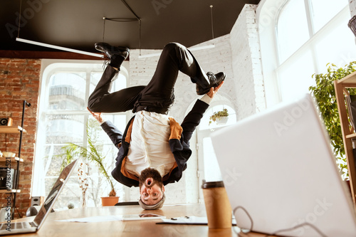 obraz PCV Young caucasian businessman having fun dancing break dance in the modern office at work time with gadgets. Management, freedom, professional occupation, alternative way of working. Loves his job.