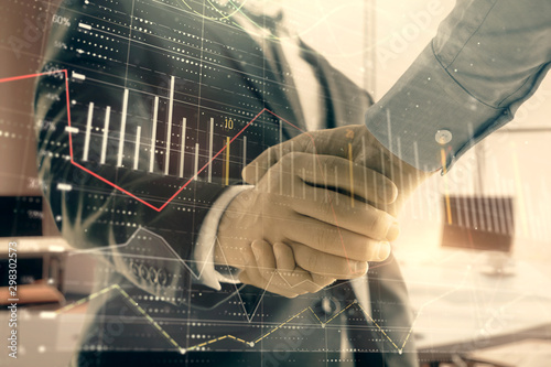 Fototapeta  Multi exposure of financial graph on office background with two businessmen handshake