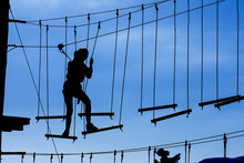 Silhouette Of Young Girl In Helmet Climbing On High Rope Course Against Blue Sky. Wooden Bars Tied To Ropes, Part Of Obstacle Course In Adventure Park