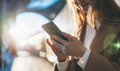 Obraz Woman holding mobile phone on sun flare platform station. Close up technology smartphone online connect. Girl travel train using gadget cellphone. Digital wifi internet lifestyle mockup - fototapety do salonu