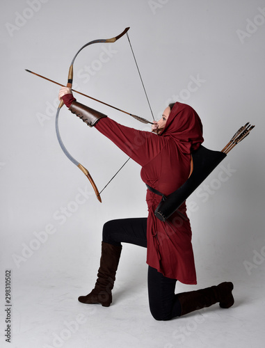 Photo full length portrait of a brunette girl wearing a red fantasy tunic with hood, holding a bow and arrow