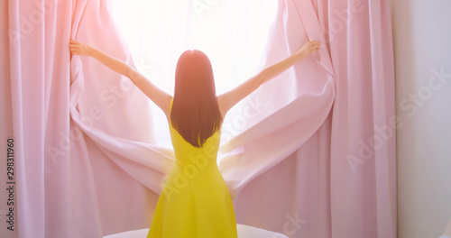 Photographie  asian woman opening curtain