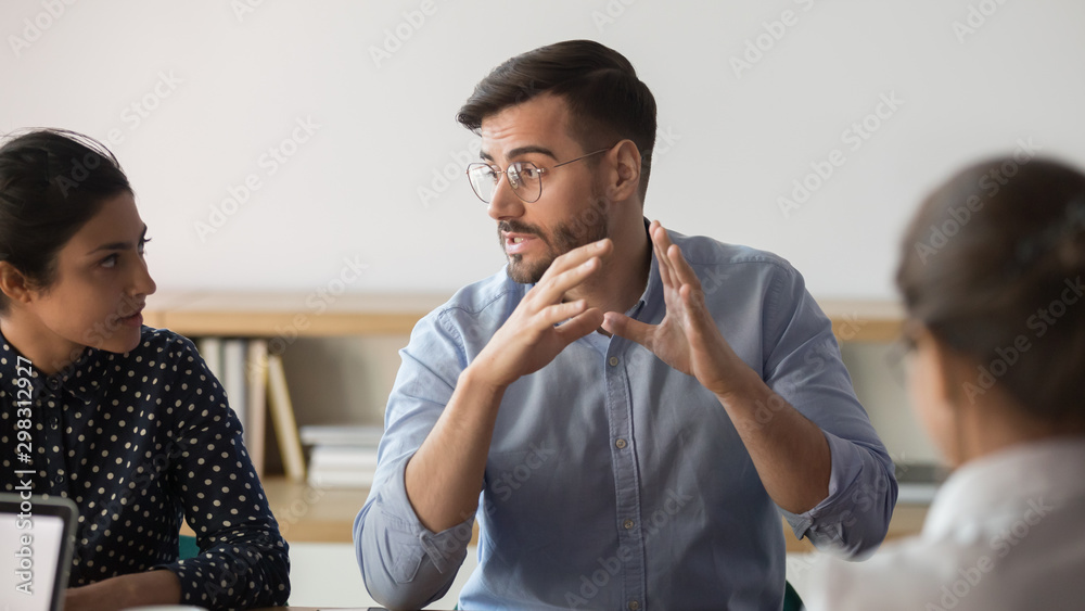 Fototapeta Confident male boss explaining ideas to diverse team at office