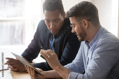 Foto  Diverse millennial employees discussing data report at office