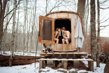 Couple Sitting In Sauna At Forest In Winter