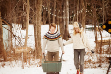 Couple With Wheelbarrow Walking On Snow Covered Field In Forest