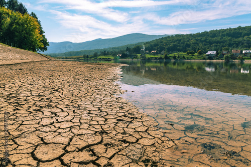 Dry cracked soil on the drying up watering place bank with animal tracks Wallpaper Mural