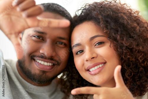 Foto  people concept - happy african american couple making selfie or viewfinder viewf