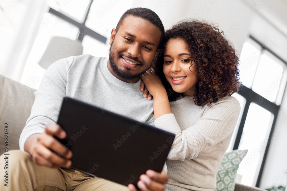 Fototapety, obrazy: technology, internet and people concept - happy african american couple with tablet computer at home