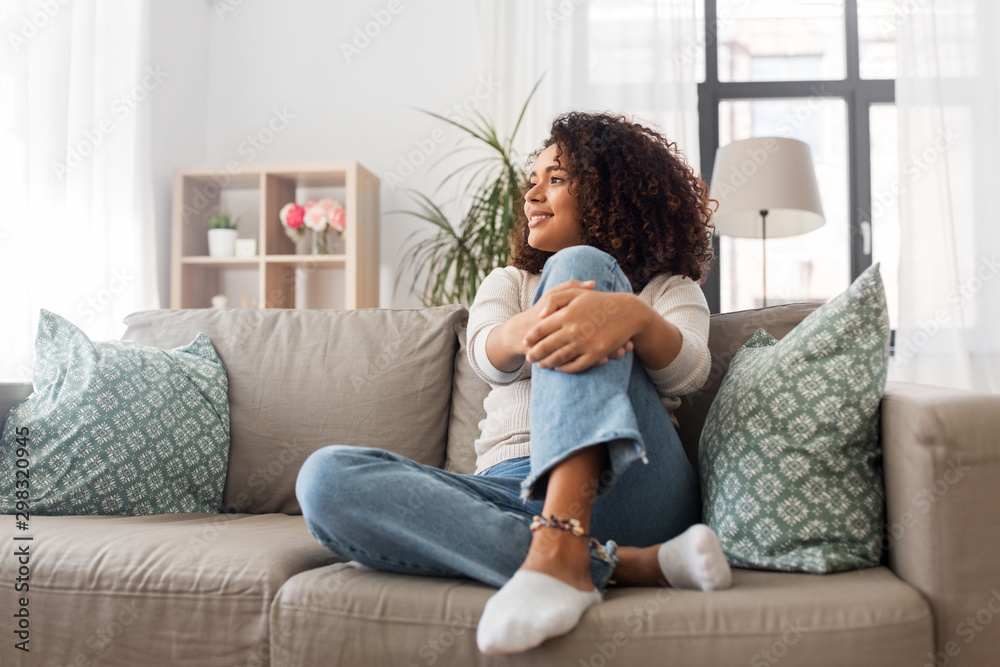 Fototapety, obrazy: people, race, ethnicity and portrait concept - happy african american young woman sitting on sofa at home