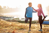 Beautiful happy young couple stretching by the lake in the early morning, warming up for jogging. Sun rising through the mist over water, rowing boats along the shore. Healthy and active lifestyle.
