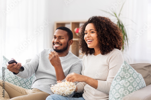 Canvastavla people and leisure concept - african american couple with popcorn watching tv at