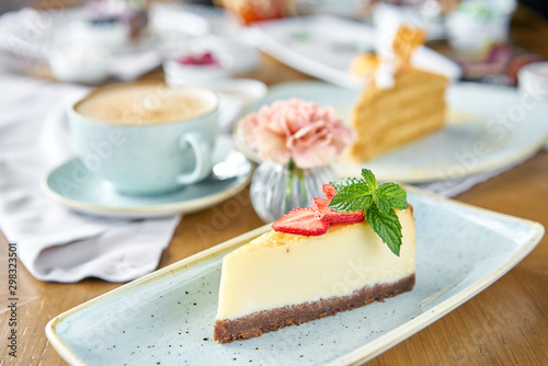 Fotografía Piece of delicious cheesecake with strawberry and mint leaves on white plate