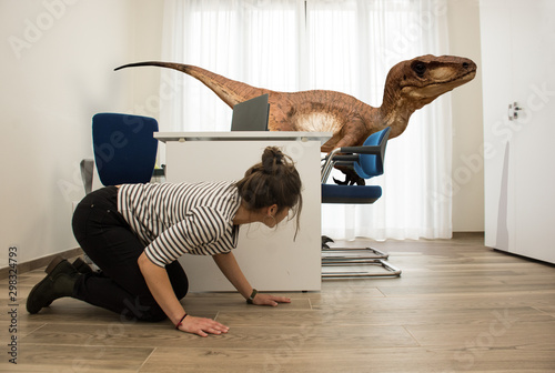 Photo A young employee hides from a velociraptor in the office where she works