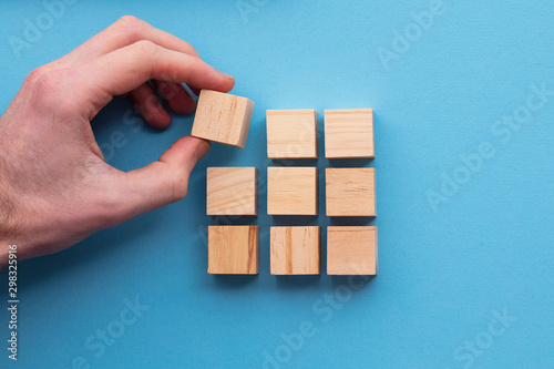 Fotografia Hand choosing a wooden block from a set. Business choice concept