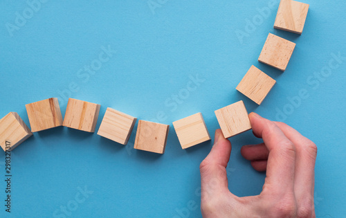 Hand choosing a wooden block from a set. Business choice concept Wallpaper Mural