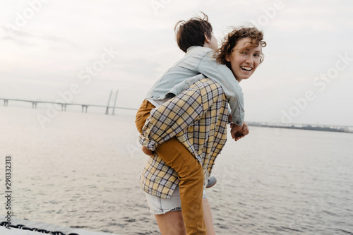 Son enjoying piggyback ride with his young mother while walking Canvas Print