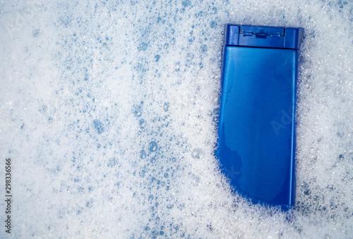 Obraz na plátně  A blue can of shampoo floats in foamy water