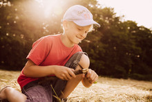 Boy Carving A Piece Of Wood On Field