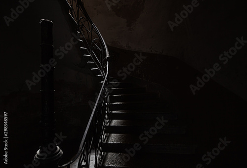 An ancient screw staircase in a dark entrance, a small ray of light illuminates the steps.