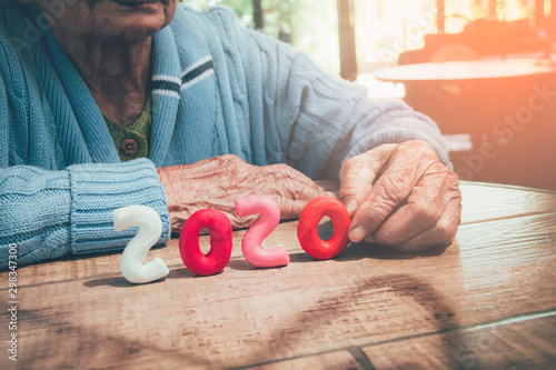 Valokuva  Old person hands holding number 2020 on wood table
