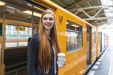 Portrait Of Redheaded Young Woman With Coffee To Go Getting Out Of Train, Berlin, Germany