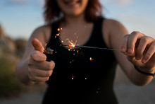 Young Woman Lights A Sparkler With A Cigarette Lighter