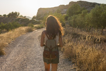 Young Woman Walks Through A Dirt Road In A Meadow
