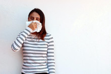 Young Woman Blowing Nose Into Tissue