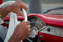 The Hands Of An Older Man At The Wheel Driving A Classic Car