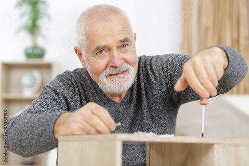 a mature man making furniture Wallpaper Mural
