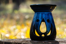 Blue Ceramic Scent Lamp Like Jack-o-lantern On A Stump In The Forest. Halloween Concept. Copy Space